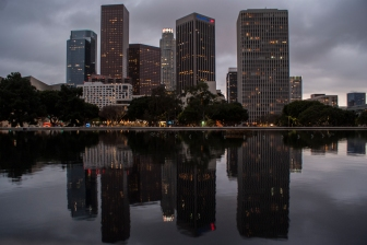 The sky dims and Los Angeles is reflected in a shallow pool surrounding the John Ferraro building.