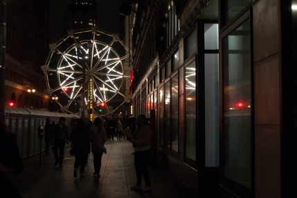 friends and strangers walk up 5th Street toward the Night on Broadway festivities in downtown Los Angeles as the lights of a ferris wheel and blinking traffic lights reflect in storefront windows.