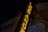A neon street sign dimly lights up the ornate details of a Broadway theater.