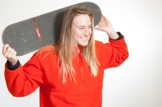 A student model's a fellow classmate's skateboard.