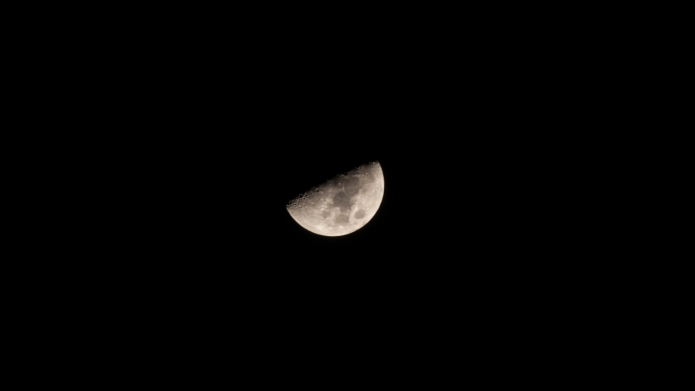 A close up on a waxing gibbous moon.