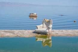 A stranded chair rests on a soft sand island in the Salton Sea.
