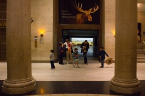 A family scurries to leave the museum at closing time.