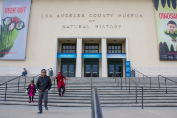 Two active children ad their father leave the Los Angeles Museum of Natural History.