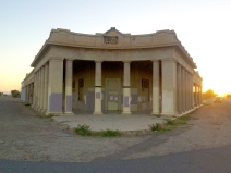 The front of Niland, California's abandoned recycling plant is highlighted by the last rays of the day's sunlight.