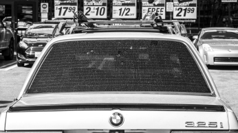 An aged and dirtied BMW sits outside of a discount store on Vermont Avenue.