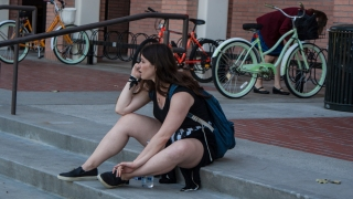 A USC Student perches atop stairs at USC's Grace Ford Salvatori Hall.